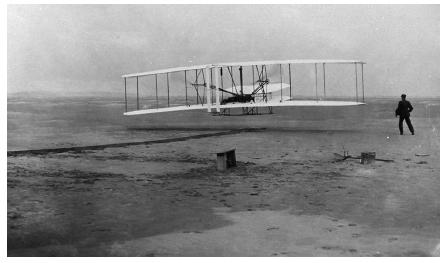 Orville Wright is at the controls as brother Wilbur looks on during the Wrights' first successful flight, on December 17, 1903, at Kitty Hawk, North Carolina. (Reproduced courtesy of the Library of Congress.)