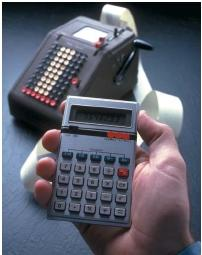 A modern hand-held calculator (foreground) and its predecessor. (Reproduced by permission of The Stock Market.)