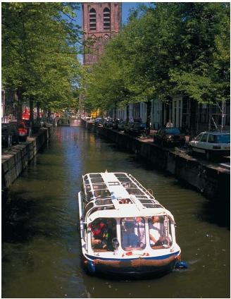 A canal boat in a narrow canal in the Netherlands. (Reproduced by permission of Photo Researchers, Inc.)