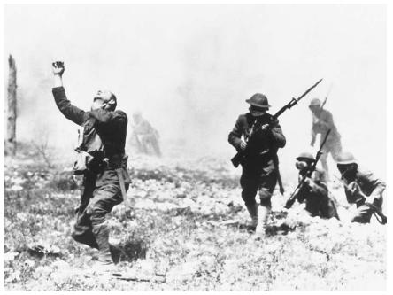 American troops wearing gas masks during World War I. The soldier at left, unable to get his mask on in time, clutches his throat as he breathes in the poisonous gas. (Reproduced by permission of the Corbis Corporation [Bellevue].)