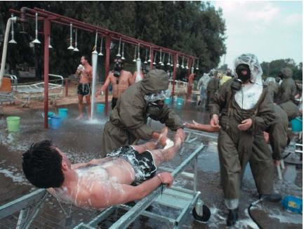 "Soldiers at Assaf Harofe Hospital washing ""victims"" in a simulated chemical warfare attack. (Reproduced by permission of the Corbis Corporation [Bellevue].)"