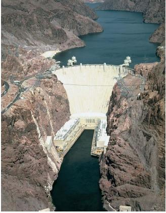 A downstream view of Hoover Dam, looking toward the east at the face of the dam. The Colorado River is in the foreground. The dam is 726 feet (221 meters) high and confines enough water in Lake Mead to cover the state of New York one foot deep. (Reproduced by permission of The Stock Market.)