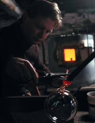 A glassblower cutting the blow pipe off the globe he just created. (Reproduced by permission of Photo Researchers, Inc.)