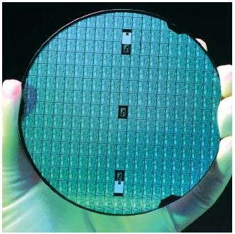 A circular wafer of silicon carrying numerous individual intergrated circuits. Multiple circuits are formed on one silicon base and later cut from it. (Reproduced by permission of Photo Researchers, Inc.)
