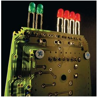 Circuit board with red and green light-emitting diode (LED) indicator lights from a radar detector. (Reproduced by permission of The Stock Market.)
