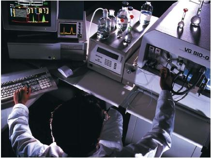 A scientist injecting a sample into a mass spectrometer. Inside, the sample will be bombarded by electrons to identify its chemical components. (Reproduced by permission of Photo Researchers, Inc.)