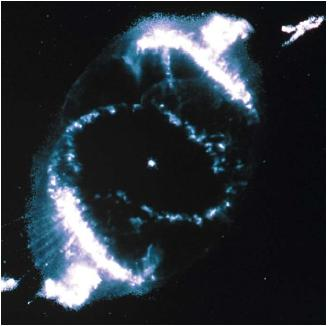The Cat's Eye Nebula as seen from the Hubble Space Telescope. At center is a dying star during its last stages of life. Knots and thin filaments can be seen along the edge of the gas. (Reproduced by permission of National Aeronautics and Space Administration.)