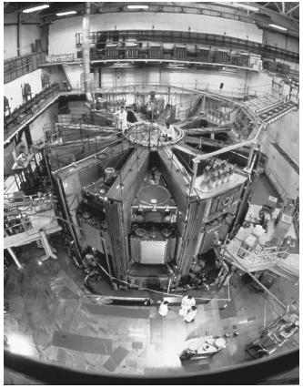 Tokamak 15, a nuclear fusion research reactor at the Kurchatov Institute in Moscow. The ring shape of the reactor is the design most favored by nuclear fusion researchers. The ring contains a plasma mixture of deuterium and tritium that is surrounded by powerful magnets that enclose the plasma with their fields and keep it away from the walls of the reactor vessel. At sufficiently high temperatures, the deuterium and tritium nuclei fuse, creating helium and energetic neutrons. It is these neutrons that carry the energy of the reactor. (Reproduced by permission of Photo Researchers, Inc.)