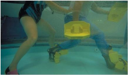 A physical therapist and patient in a water therapy pool. The patient has plastic attachments on his hands and feet that resist movement through the water, allowing him to build strength and flexibility. (Reproduced by permission of Photo Researchers, Inc.)