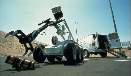 A police robot handling a live bomb by remote control. (Reproduced by permission of Photo Researchers, Inc.)
