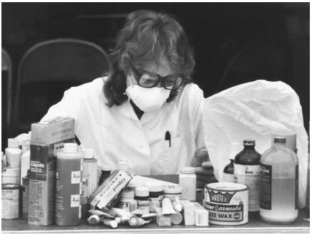 An employee at a hazardous waste collection site in Santa Cruz County, California, sorting through household hazardous waste items. (Reproduced by permission of Photo Researchers, Inc.)