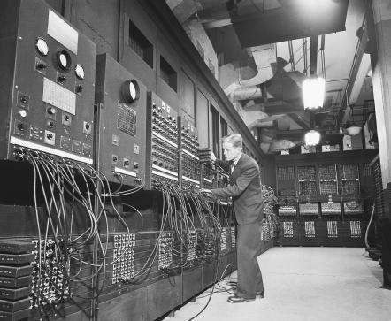 Dr. J.W. Mauchly makes an adjustment to ENIAC, the massive computer he designed to assist the U.S. military during World War II.